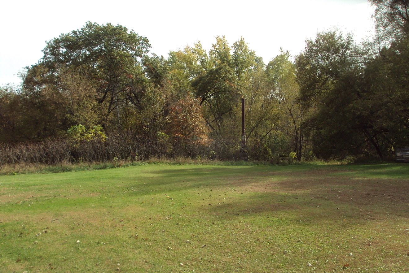 On the former Bar L golf course grounds. The bulk of the golf grounds is now grown over with trees and brush, though it's fairly easy to conceive where the holes might have been routed. The smokestack to the right and in the background (click on the photo for a larger view) is all that remains of Augie's Hayloft.